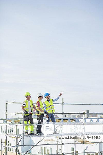 Architekt  der Kollegen etwas zeigt  während er auf einem Gerüst gegen den Himmel steht.