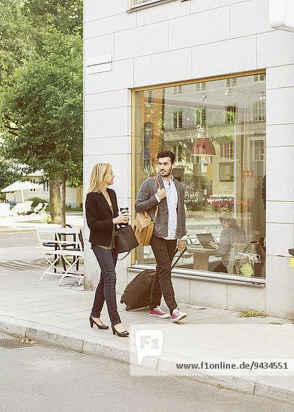 Volle Länge der Geschäftskollegen mit Gepäck auf dem Gehweg