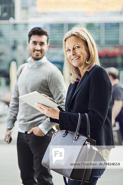 Portrait einer Geschäftsfrau mit digitalem Tablett auf der Stadtstraße mit Kollegin im Hintergrund