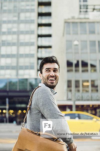 Glücklicher Geschäftsmann schaut weg  während er die Umhängetasche auf der Straße trägt. Glücklicher Geschäftsmann schaut weg, während er die Umhängetasche auf der Straße trägt.