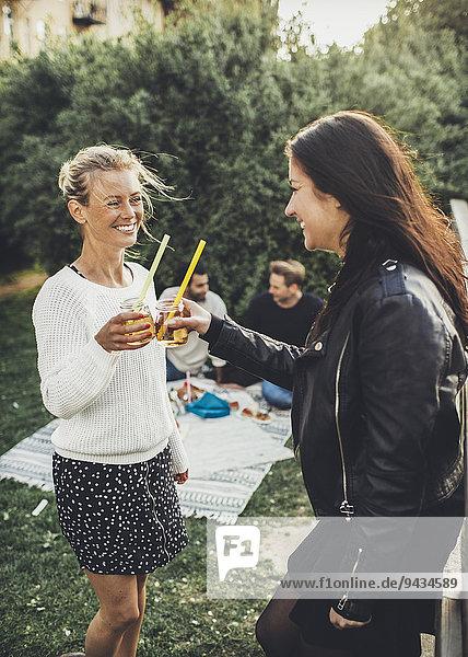 Fröhliche Freundinnen toasten Holunderblütengetränke auf der Dachparty