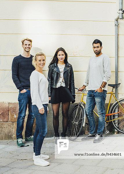 Ganzkörperporträt von Freunden  die mit dem Fahrrad auf dem Bürgersteig stehen