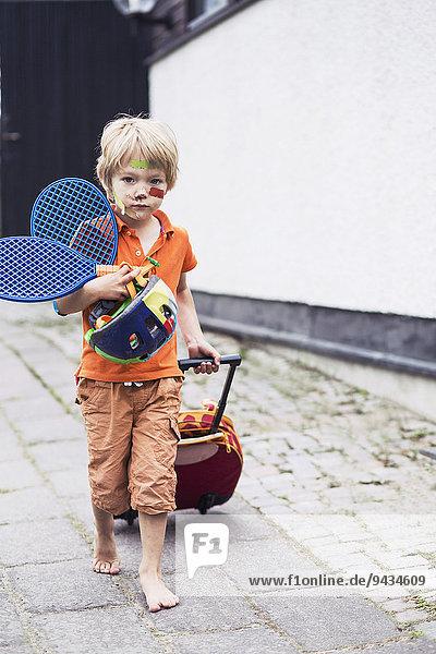 Ganzflächiges Porträt des Jungen  der Gepäck zieht  während er Tennisschläger und Helm auf der Straße hält.
