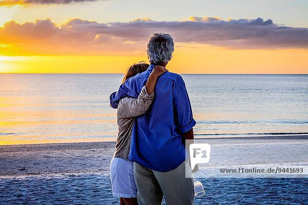 Retired couple enjoy a romantic walk on Siesta Key beach at sunset.