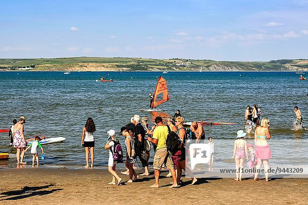 Fröhlichkeit Mensch Menschen gehen Strand Meer paddeln vorwärts Weymouth