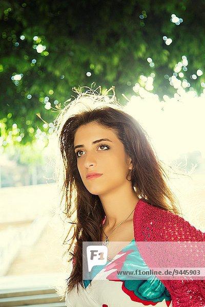 Beautiful young woman looking away outdoors.