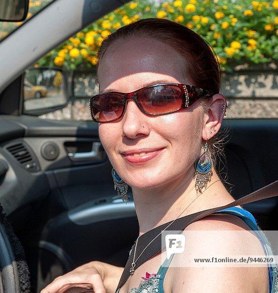 Frau lächeln Auto fahren Blick in die Kamera Kleidung Sonnenbrille alt rothaarig Jahr