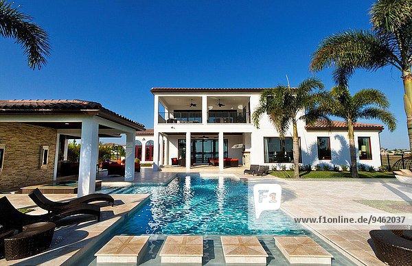 Beautiful pool and lake behind luxury upscale home in Windermere  Florida.
