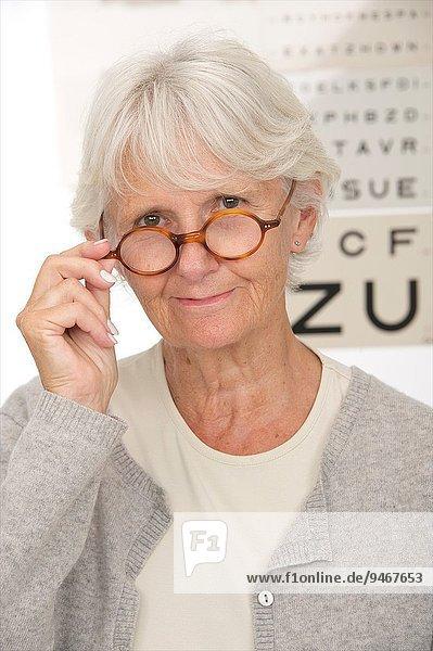Senior woman testing her eyesight and choosing glasses