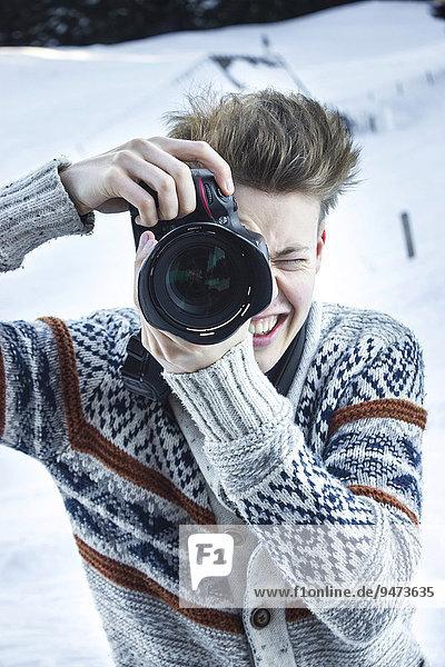 Junger Mann im Schnee fotografiert mit digitaler Spiegelreflexkamera  Hochbrixen  Brixen im Thale  Tirol  Österreich  Europa