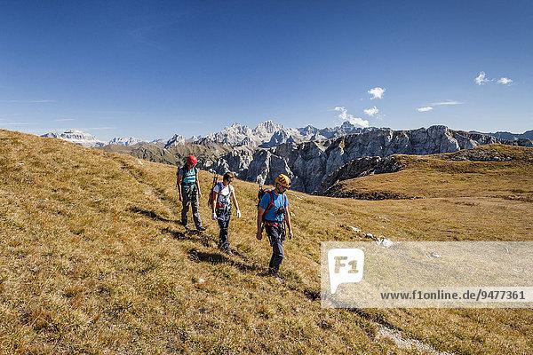 Bergsteiger beim Aufstieg auf die Cima Valacia über den Klettersteig Via Ferrata F. Gadotti im Val San Nicolo im Fassatal  hinten die Sellagruppe und die Marmolata-Südwand  Dolomiten  Pozza di Fassa  Trentino  Trentino-Alto Adige  Italien  Europa