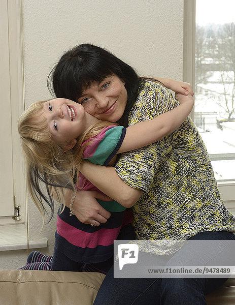 Mädchen  5 Jahre und Mutter  35 Jahre  umarmen einander
