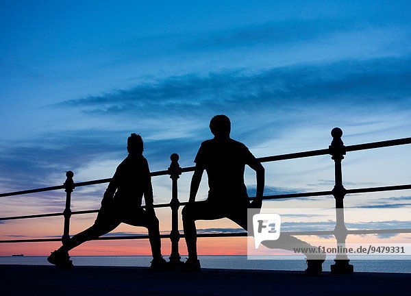 Male and female joggers stretching at sunrise at Seaton Carew on the north east coast of England  United Kingdom.