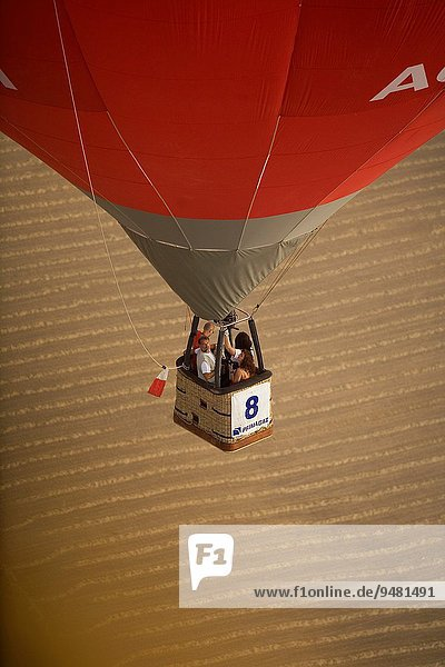 Red balloon flying over a wheat field in European hot air balloon festival Igualada  Barcelona  Catalonia  Spain  Europe.