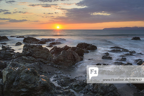Sonnenuntergang am Pazifik  Felsen von Wasser umspült  hinten Halbinsel Osa  Golfo Dulce  Provinz Puntarenas  Costa Rica  Nordamerika