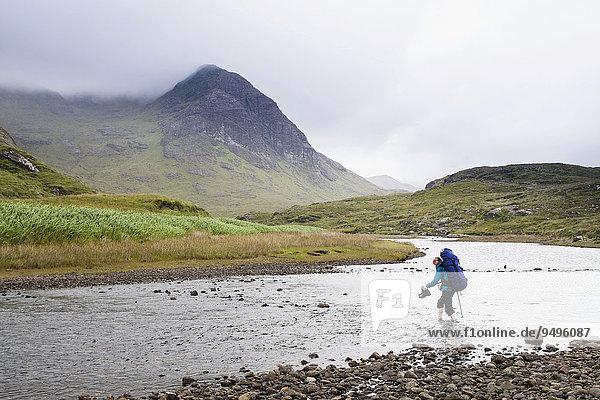 Frau mit Rucksack durchquert den Fluss Abhainn Camas Fhionnairigh  hinten Sgurr Hain  Camasunary  Isle of Skye  Schottland  Großbritannien  Europa