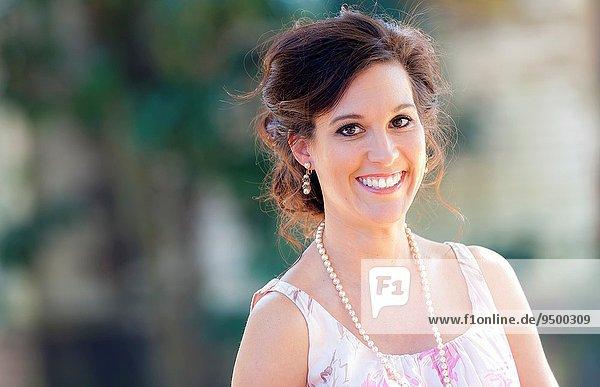 Außenaufnahme Portrait Frau sehen lächeln braunhaarig Blick in die Kamera gerade alt freie Natur Jahr
