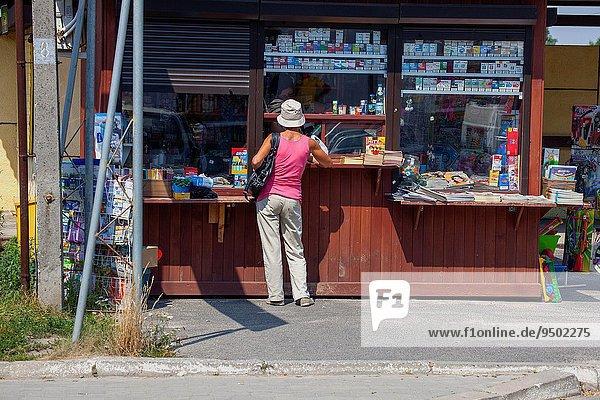 Außenaufnahme Frau klein Weg Zigarette kaufen verkaufen polieren Kiosk polnisch