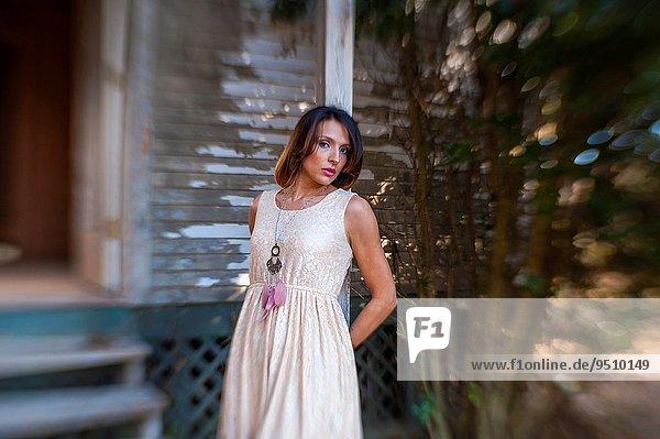 stehend Frau sehen Wohnhaus frontal braunhaarig Blick in die Kamera Kleidung 30 Kleid alt Jahr