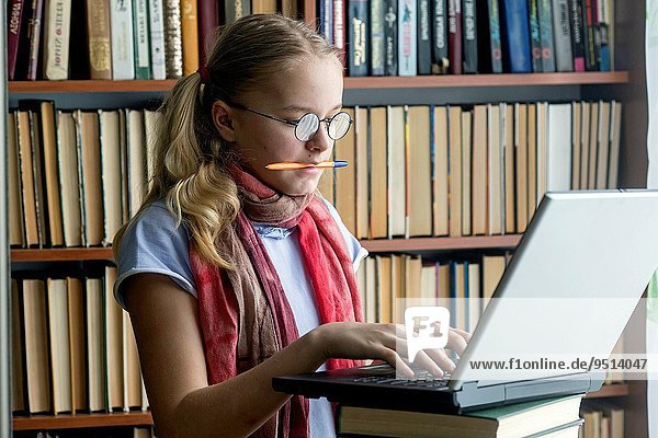Girl with a computer in the reading room.