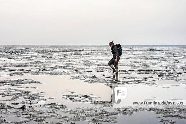 Eine junge Frau läuft über das Watt im Wattenmeer bei Ebbe  Husum  Nordfriesland  Schleswig-Holstein  Deutschland  Europa