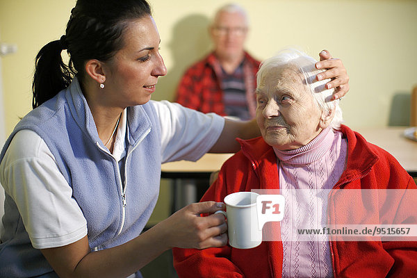 Woman  88 years  in a nursing home  at breakfast  supported by a geriatric nurse  Kralovske Porici  Bohemia  Czech Republic  Europe