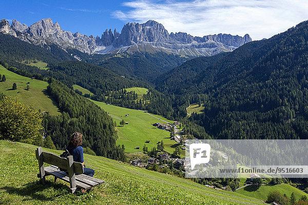 Frau auf Bank  hinten Rosengartengruppe und Dorf  Tiers  Provinz Südtirol  Italien  Europa
