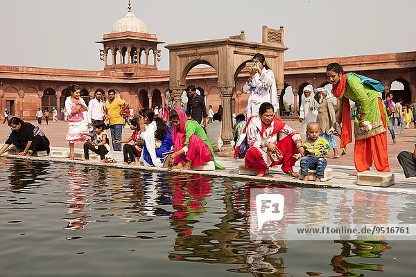 Devout Muslims purifying themselves in the water basin of the Friday Mosque Jama Masjid  Delhi  India  Asia