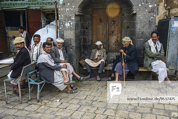 Men sitting in front of a house in the old city  Sana'a  Yemen  Asia