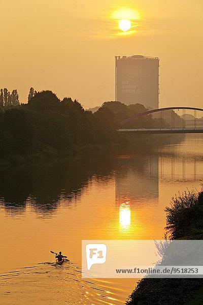 Ein Kanufahrer auf dem Rhein-Herne-Kanal mit Gasometer bei Sonnenuntergang  Oberhausen  Ruhrgebiet  Nordrhein-Westfalen  Deutschland  Europa