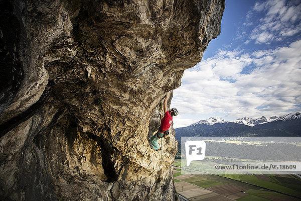 Freikletterer mit Helm klettert im Vorstieß an einer Felswand  Martinswand  Galerie  Innsbruck  Tirol  Österreich  Europa