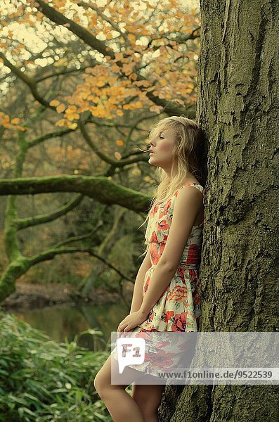 Beautiful young woman leaning against a tree.
