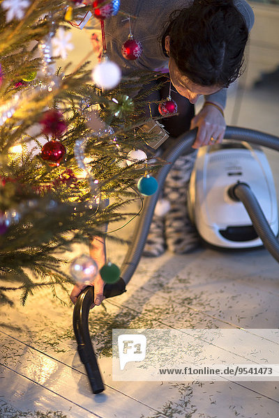 Woman hovering needles under Christmas tree