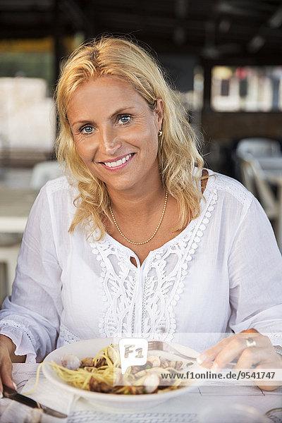 Frau Speisefisch und Meeresfrucht Pasta Nudel essen essend isst