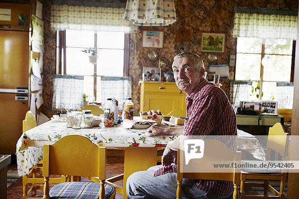 Senior Senioren Mann am Tisch essen Tisch