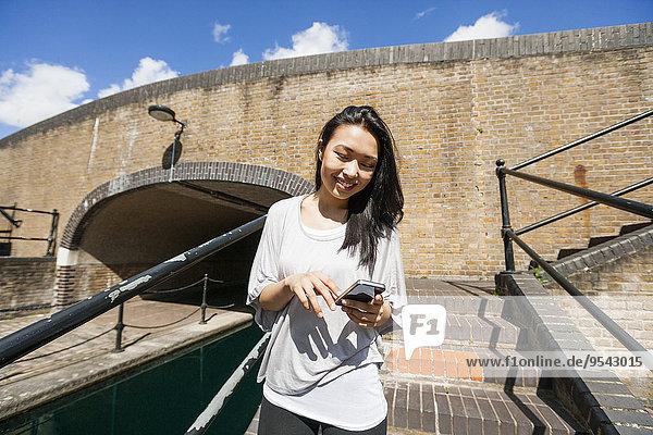 Stufe junge Frau junge Frauen benutzen lächeln Smartphone