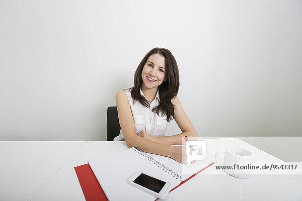 Portrait Geschäftsfrau Schreibtisch schreiben lächeln Aktenordner - Behälter Büro jung