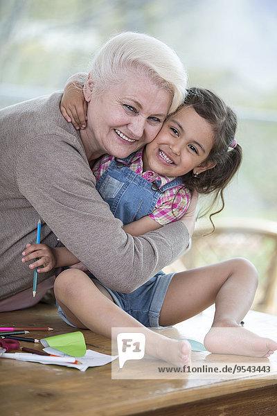 sitzend Interior zu Hause Senior Senioren Portrait Frau umarmen Enkeltochter Tisch