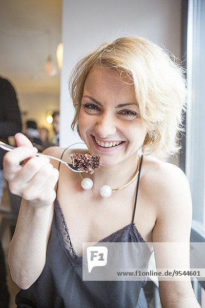 junge Frau junge Frauen Portrait Fröhlichkeit Cafe essen essend isst Gebäck