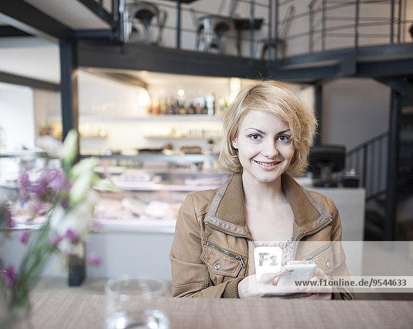 Handy junge Frau junge Frauen benutzen Portrait Fröhlichkeit Cafe