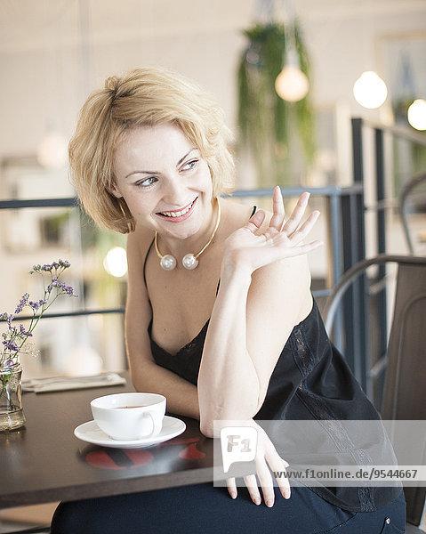 junge Frau junge Frauen Fröhlichkeit Restaurant winken Tisch