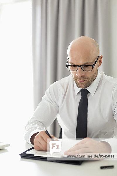 Geschäftsmann Klemmbrett schreiben Mittelpunkt Erwachsener Heimarbeitsplatz