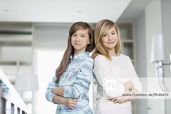 Portrait of cute sisters standing together at home