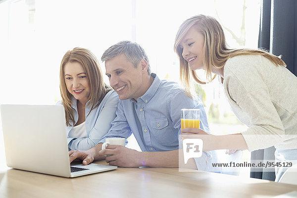Interior zu Hause benutzen Fröhlichkeit Notebook Menschliche Eltern Tochter