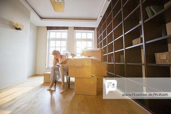 Ganzansicht sitzend Frau Wohnhaus Streß Pappschachtel Pappkarton Pappe neu
