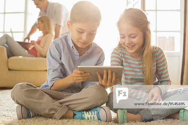 benutzen Fröhlichkeit Boden Fußboden Fußböden Menschliche Eltern Hintergrund Tablet PC Geschwister