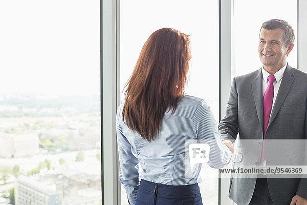 Geschäftsfrau Geschäftsmann lächeln Büro schütteln