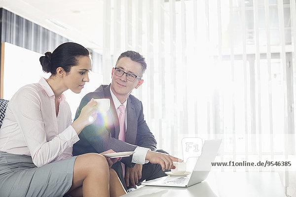 Geschäftsfrau Diskussion Notebook Geschäftsmann über Büro