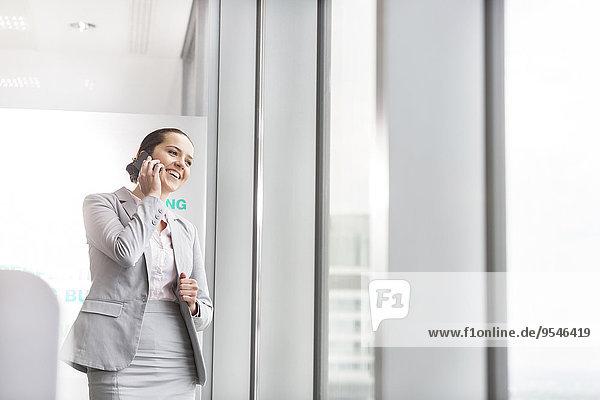 Handy nahe Geschäftsfrau sprechen Fenster lächeln Büro jung