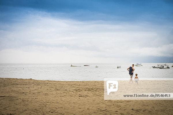 Mexiko  Mann mit Kleinkind  der am Strand spazieren geht.